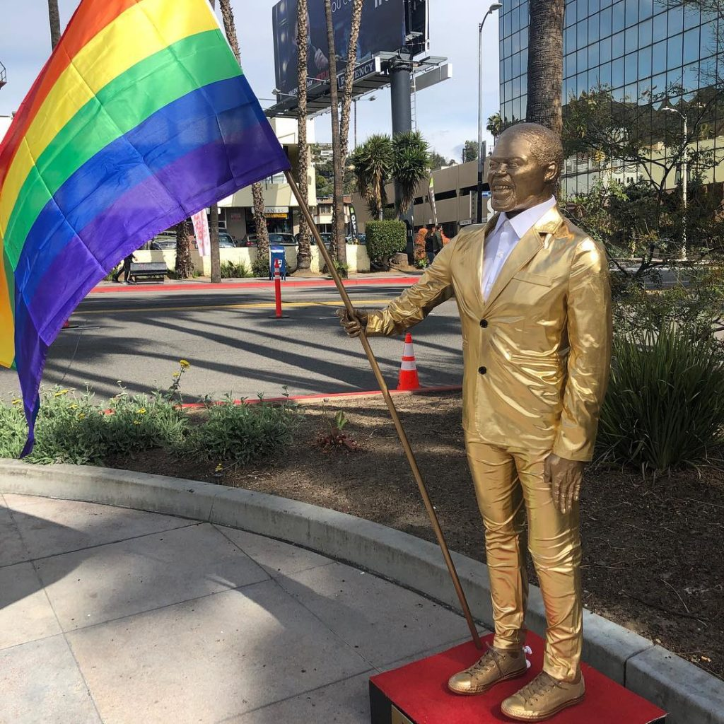 Photo of the Kevin Hart statue holding a rainbow flag.