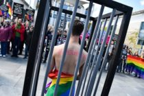 An activist stands naked, wrapped in a rainbow flag, in a mock cage in front of the Chancellery in Berlin on April 30, 2017, during a demonstration calling on Russian President to put an end to the persecution of gay men in Chechnya.