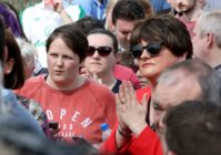 Sara Canning (L), partner of killed journalist Lyra McKee, stands beside Democratic Unionist Party (DUP) leader Arlene Foster (R) at a gathering to condemn McKee's killing near the scene of rioting violence in the Creggan area of Derry in Northern Ireland