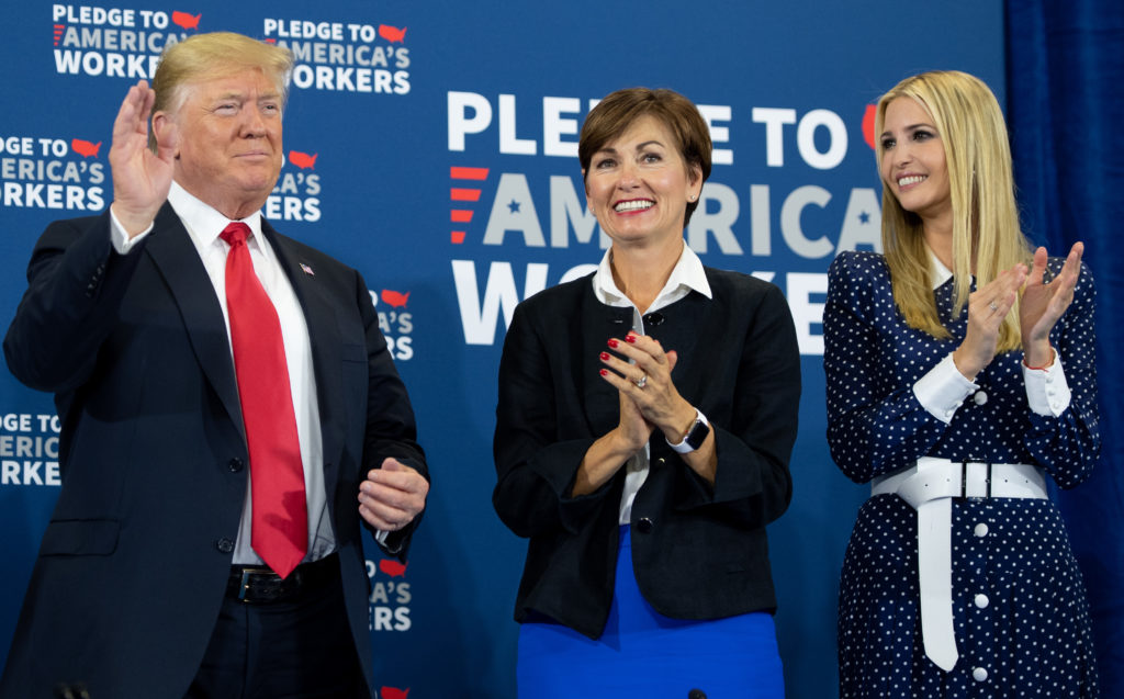 Iowa Governor Kim Reynolds (C) pictured between President Donald Trump (L) and his daughter Ivanka Trump (R), as he holds a roundtable discussion on workforce development at Northeast Iowa Community College in Peosta, Iowa, July 26, 2018.