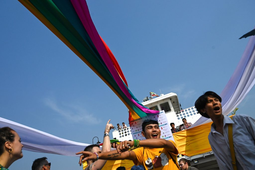 Members of the lesbian, gay, bisexual, and transgender (LGBT) community dance and take selfies under rainbow flags displayed on a boat during the Pride Boat Parade, an event of the Myanmar's Yangon Pride festival in Yangon on January 26, 2019.