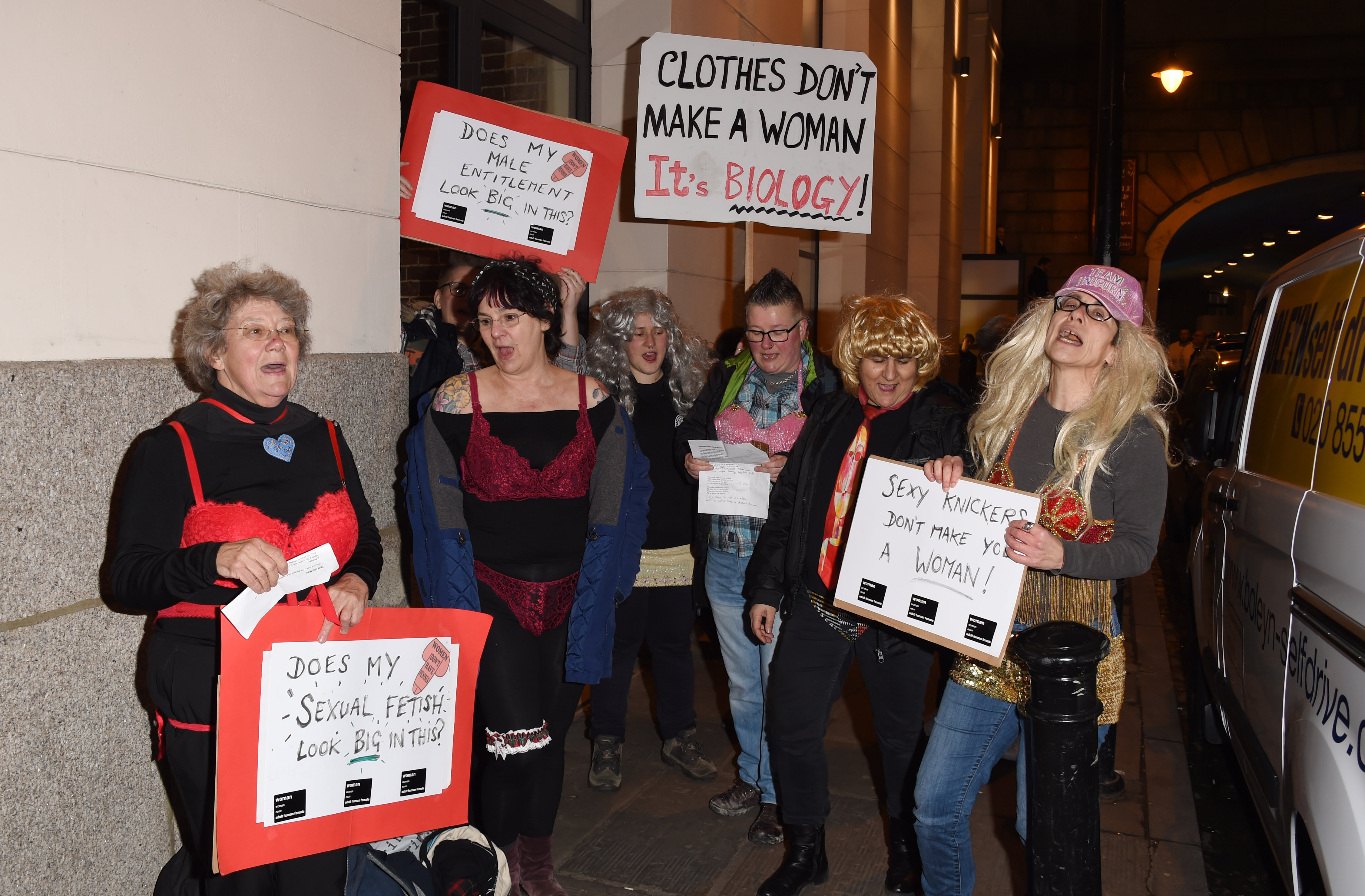anti-trans protesters picket a transgender lingerie show