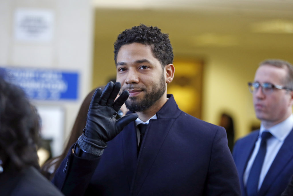 Actor Jussie Smollett waves as he follows his attorney to the microphones after his court appearance at Leighton Courthouse on March 26, 2019 in Chicago, Illinois.