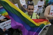 "A protestor waves the gay pride flag as others hold banners during an anti-homophobia rally in Beirut on April 30, 2013. Lebanese homosexuals, human rights activists and members from the NGO Helem (the Arabic acronym of ""Lebanese Protection for Lesbians, Gays, Bisexuals and Transgenders"") rallied to condemn the arrest on the weekend of three gay men and one transgender civilian in the town of Dekwaneh east of Beirut at a nightclub who were allegedly verbally and sexually harassed at the municipality headquarters. AFP PHOTO/JOSEPH EID (Photo credit should read JOSEPH EID/AFP/Getty Images)"