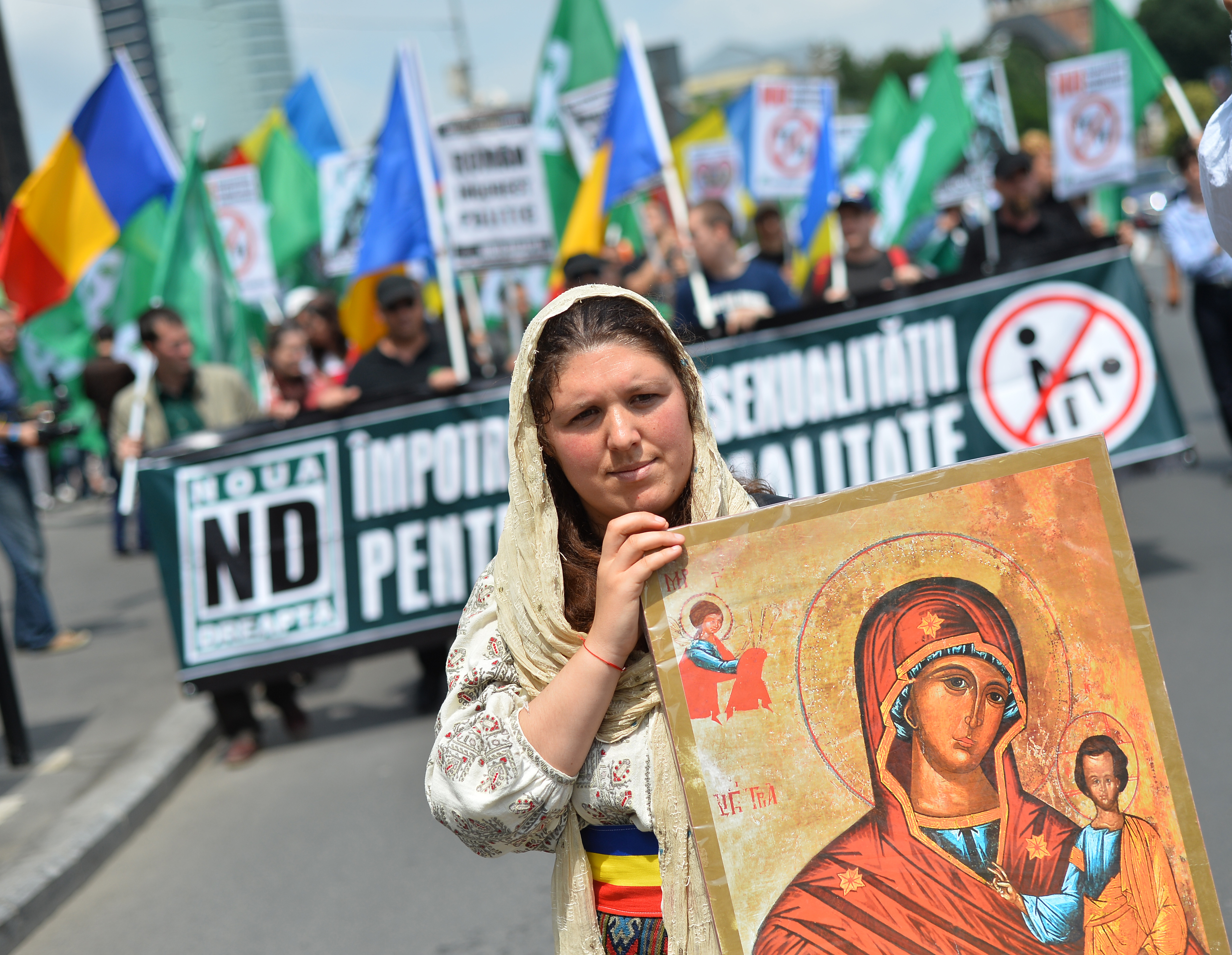 A Romanian woman holds an Orthodox icon as she marches with Romanian flag during a protest against incoming Gay Pride in Bucharest on June 8, 2013.