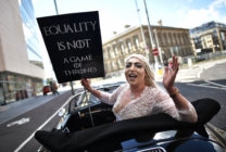 """A drag queen hlding a sign saying """"Equality is not a game of thrones"""" takes part in Belfast's gay pride protesting Northern Ireland's ban on same sex marriage."""