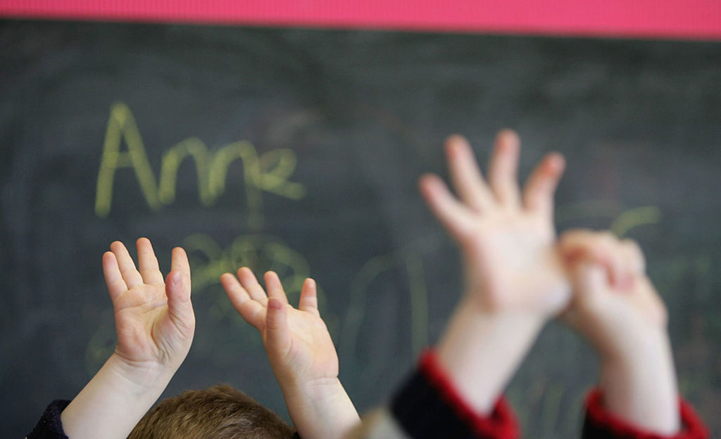 Children in school raise their hands as they learn about LGBT relationships.