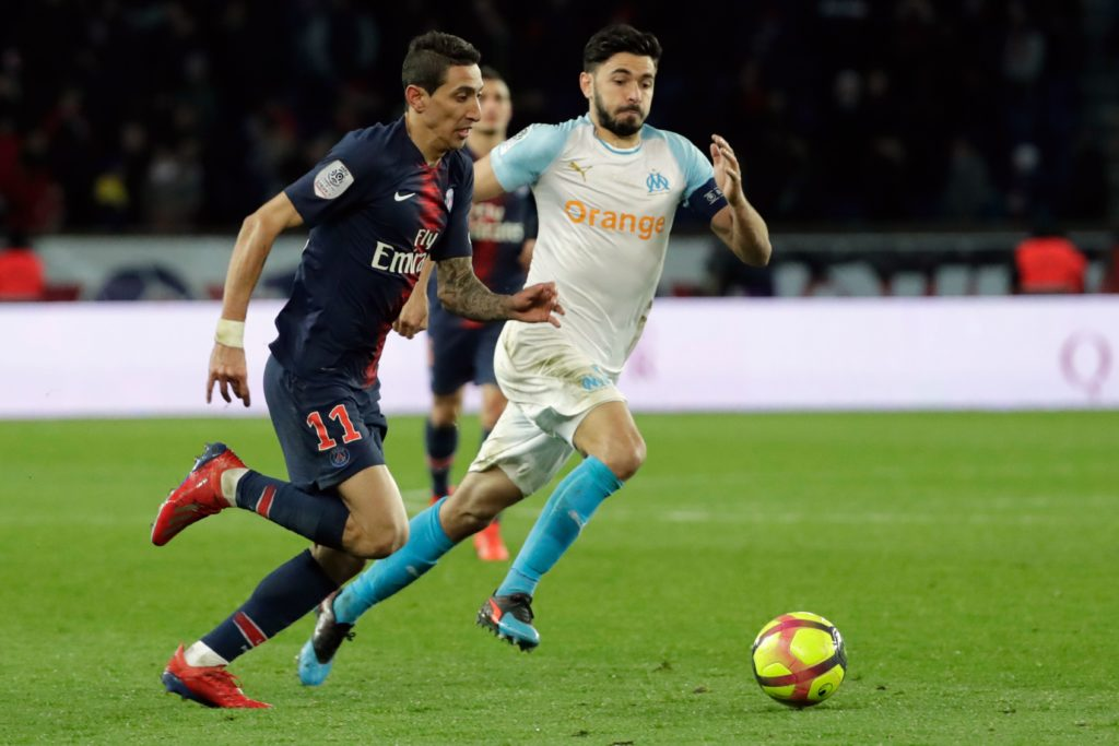 Paris Saint-Germain's Angel Di Maria vies with Marseille's Morgan Sanson for a ball.