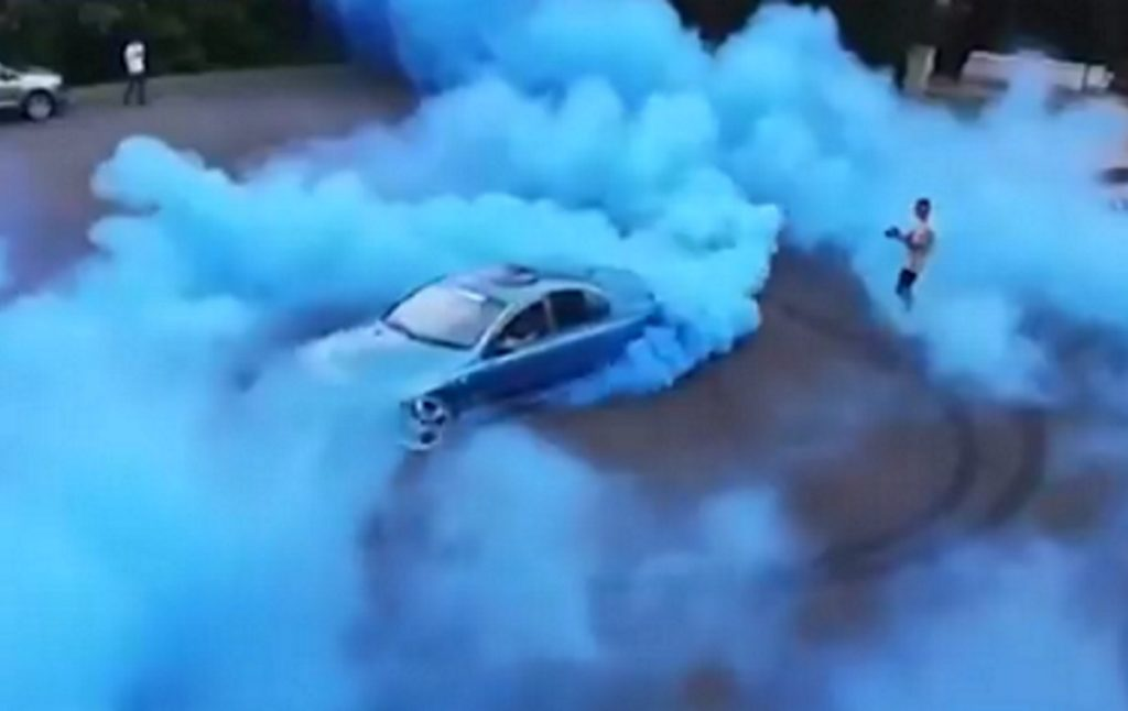 A man drives a car to perform a gender reveal while another man films it.