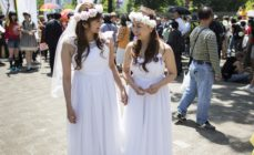A Japanese same-sex couple in wedding attire takes part in the Tokyo Rainbow Pride Parade on May 6, 2018 in Tokyo, Japan