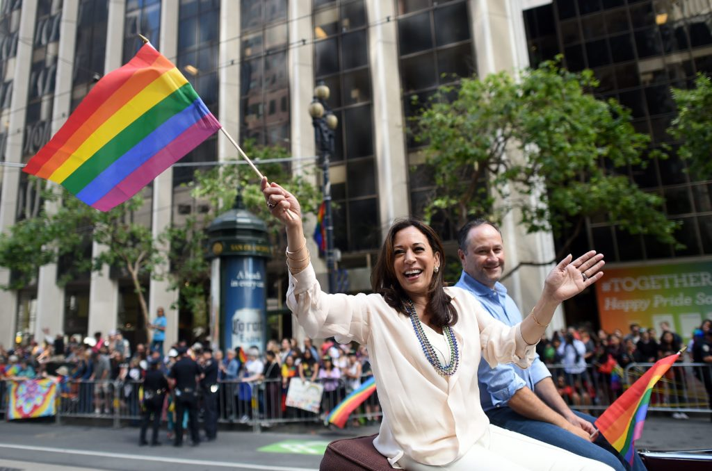 Kamala Harris waves a rainbow flag while participating in the San Francisco Pride parade in San Francisco, California on Sunday, June, 26 2016
