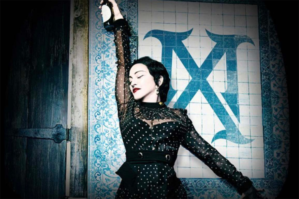Madonna as Madame X, standing against a wall
