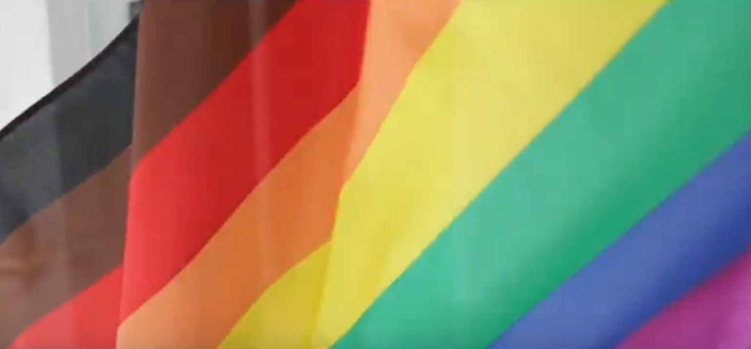 A still of Manchester Pride's promotional video, featuring an eight-striped Pride flag