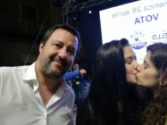 Matteo Salvini next to two women kissing.