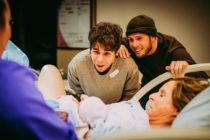 Matthew Eledge and husband Elliot Dougherty look on as Cecile Reynek Eledge holds newborn Uma Louise Dougherty-Eledge.