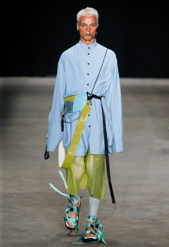 Tales Soares walking a catwalk in a blue shirt and green trousers