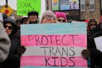 "A woman holding a sign which says ""protect trans kids"""