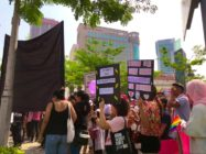 Protesters hold pro-equality signs and LGBT flags at the women's march in Malaysia