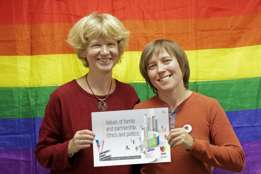 Founders Anna and Yulia pose with the logo for this year's conference, which did not go ahead as planned after LGBT+ activists were targeted in an attack.