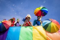 A giant rainbow flag being carried along Brighton seaside