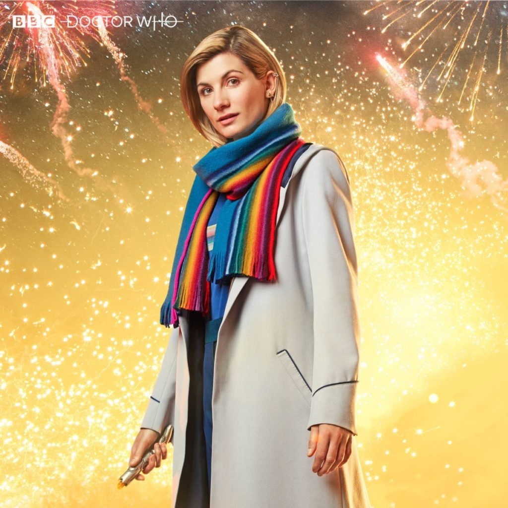 Jodie Whittaker as the Doctor in Doctor Who, wearing a rainbow scarf