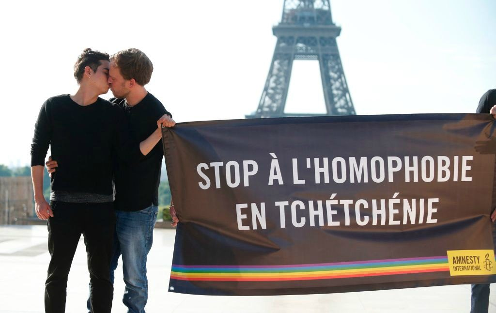 Gay men kiss in front of Eiffel Tower