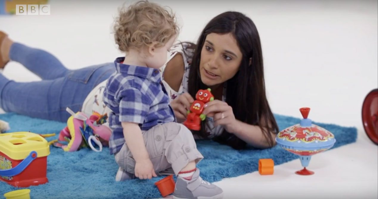 Child and adult play with a robot toy