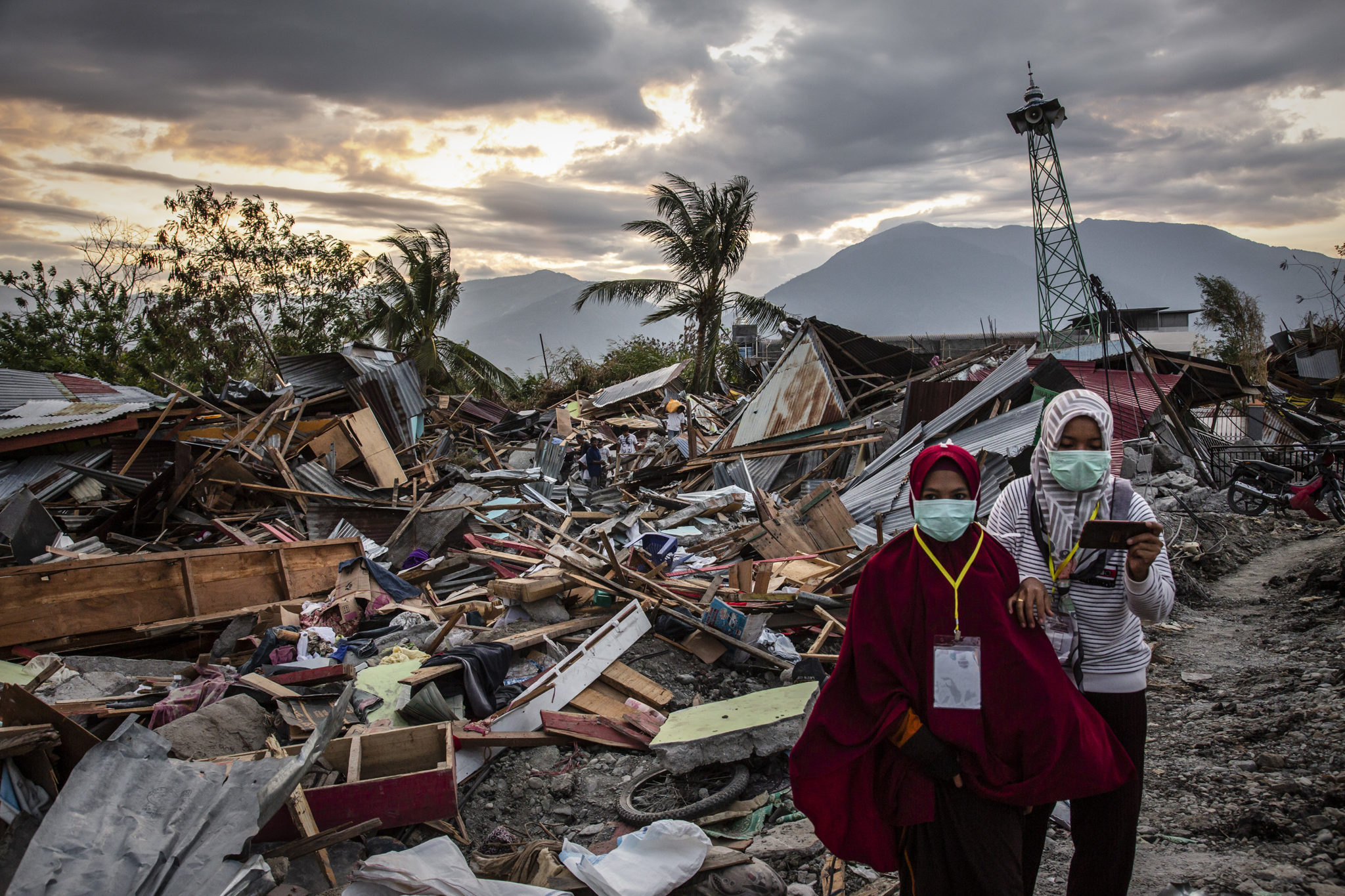 PALU, INDONESIA - OCTOBER 05: People walk along a damaged area which was hit by liquefaction in Petobo village following the earthquake on October 5, 2018 in Palu, Central Sulawesi, Indonesia. The death toll from last weeks earthquake and tsunami has risen to at least 1,558 but widely expected to rise as officials said on Friday the number of victims of the liquefaction could be up to a thousand. Power had returned to parts of the city and fuel shipments have begun to flow back but some affected towns remain inaccessible with the infrastructure badly damaged. A tsunami triggered by a magnitude 7.5 earthquake slammed into Indonesia's coastline on the island of Sulawesi which destroyed or damaged over 70,000 homes as tensions remain high with desperate survivors trying to secure basics like clean water and fuel for generators. (Photo by Ulet Ifansasti/Getty Images)