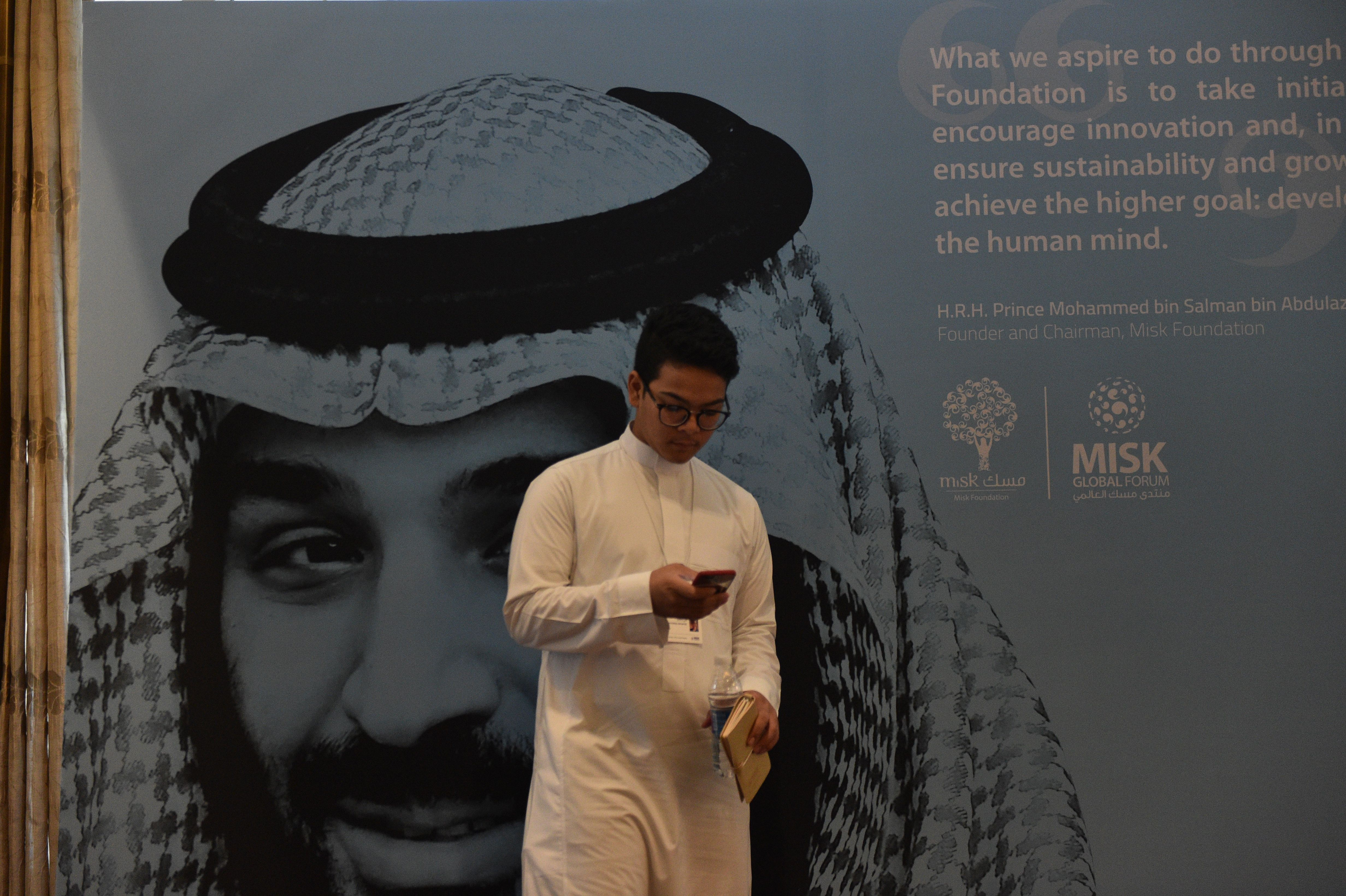 A young man in Saudi Arabia, where textbooks teach gay sex is punishable by death, stands in front of a portrait of Saudi Crown Prince Mohammed bin Salman.