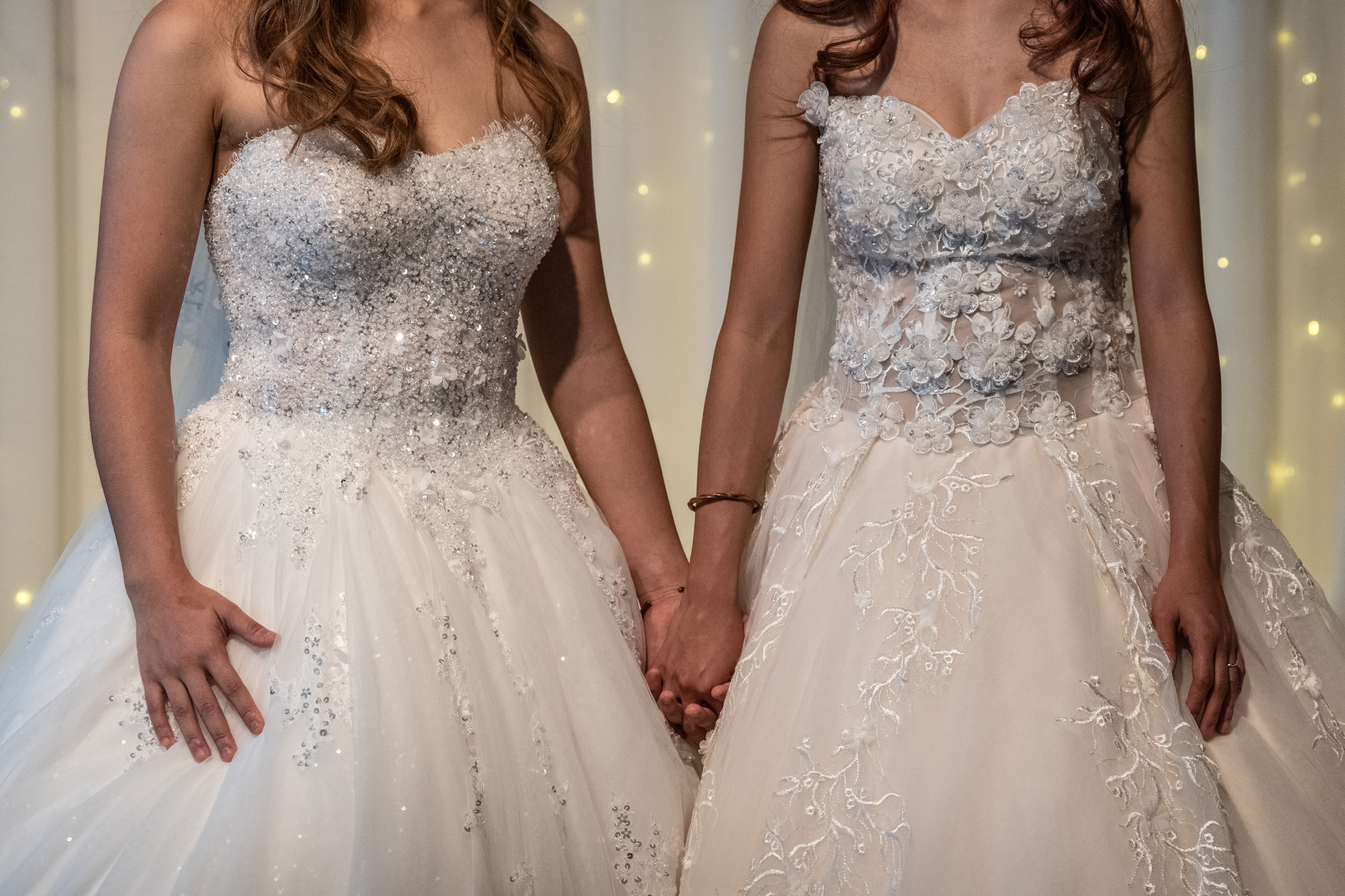 Lesbian couple hold hands wearing wedding dresses.
