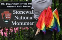 A National Park Service ranger places rainbow flags on the fence at the Stonewall National Monument in the West Village neighborhood of Greenwich Village in Lower Manhattan, New York City on June 19, 2019.