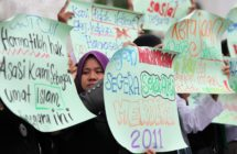 Protesters raise placards during a protest outside a corridor Mosque in Shah Alam near Kuala Lumpur on November 4, 2011. The demonstration was to urge the goverment to give recognition to the lesbian, gay, bisexual and transgender (LGBT) community. AFP PHOTO/MOHD RASFAN (Photo credit should read MOHD RASFAN/AFP/Getty Images)