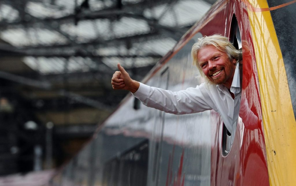 British entrepreneur Sir Richard Branson leans out of the window of the driver's cab on board a Virgin Pendolino train at Lime Street Station in Liverpool, north-west England, on March 13, 2012, as he prepares to launch a Global Entrepreneurship Congress. The event aims to be the largest gathering of start-up champions from around the world. AFP PHOTO/PAUL ELLIS (Photo credit should read PAUL ELLIS/AFP/Getty Images)