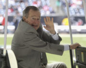 Former U.S. President George H.W. Bush waves during the game between the New England Patriots and the Houston Texans at Reliant Stadium on December 1, 2013 in Houston, Texas.
