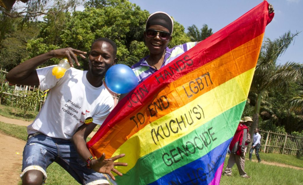 "Ugandan men hold a rainbow flag reading ""Join hands to end LGBTI (Lesbian Gay Bi Trans Intersex - called Kuchu in Uganda) genocide"" as they celebrate on August 9, 2014 during the annual gay pride in Entebbe, Uganda. Uganda's attorney general has filed an appeal against the constitutional court's decision to overturn tough new anti-gay laws, his deputy said on August 9. Branded draconian and ""abominable"" by rights groups but popular domestically, the six-month old law which ruled that homosexuals would be jailed for life was scrapped on a technicality by the constitutional court on August 1. AFP PHOTO/ ISAAC KASAMANI (Photo credit should read ISAAC KASAMANI/AFP/Getty Images)"