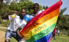 "Uganda men hold a rainbow flag reading ""Join hands to end LGBTI (Lesbian Gay Bi Trans Intersex - called Kuchu in Uganda) genocide"" as they celebrate on August 9, 2014 during the annual gay pride in Entebbe, Uganda. Uganda's attorney general has filed an appeal against the constitutional court's decision to overturn tough new anti-gay laws, his deputy said on August 9. Branded draconian and ""abominable"" by rights groups but popular domestically, the six-month old law which ruled that homosexuals would be jailed for life was scrapped on a technicality by the constitutional court on August 1. AFP PHOTO/ ISAAC KASAMANI (Photo credit should read ISAAC KASAMANI/AFP/Getty Images)"