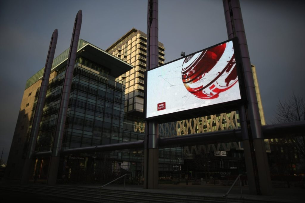 SALFORD, ENGLAND - JANUARY 05: A giant outdoor television screen broadcasts the BBC News at Media City in Salford Quays which is home to the BBC, ITV television studios and also houses many media production companies on January 5, 2015 in Salford, England. The BBC and neighbour ITV Granada with its cobbled street studios of ITV soap opera 'Coronation Street', line the banks of the Manchester Ship Canal.
