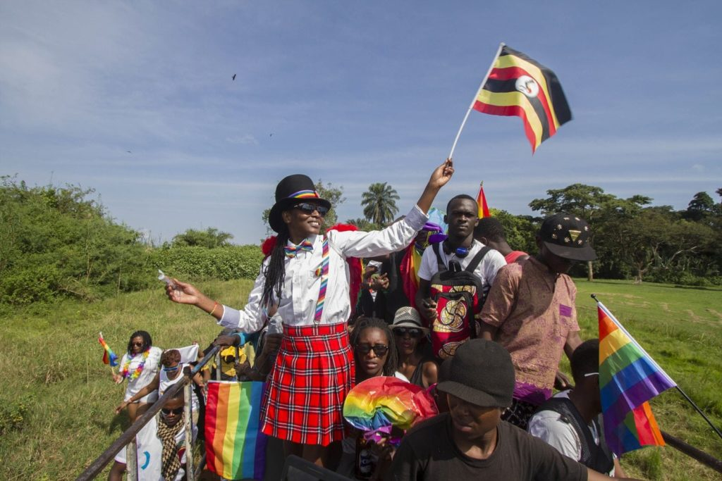 People waving Ugandan and rainbow flags take part in the Gay Pride parade in Entebbe on August 8, 2015. Ugandan activists gathered for a gay pride rally, celebrating one year since the overturning of a strict anti-homosexuality law but fearing more tough legislation may be on its way. Homosexuality remains illegal in Uganda, punishable by a jail sentence. AFP PHOTO/ ISAAC KASAMANI (Photo credit should read ISAAC KASAMANI/AFP/Getty Images)