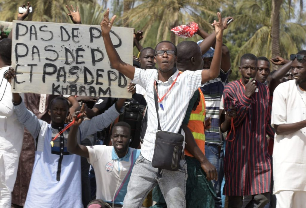 "A protestor gestures on January 22, 2015 in Dakar during a demonstration against homosexuality. Under Senegalese law, anyone convicted of an ""improper or unnatural act with a person of the same sex"" faces up to five years in jail. The government has repeatedly ruled out legalising homosexuality in the deeply conservative Muslim-majority country. Banner reads ""No fag"". / AFP / SEYLLOU (Photo credit should read SEYLLOU/AFP/Getty Images)"