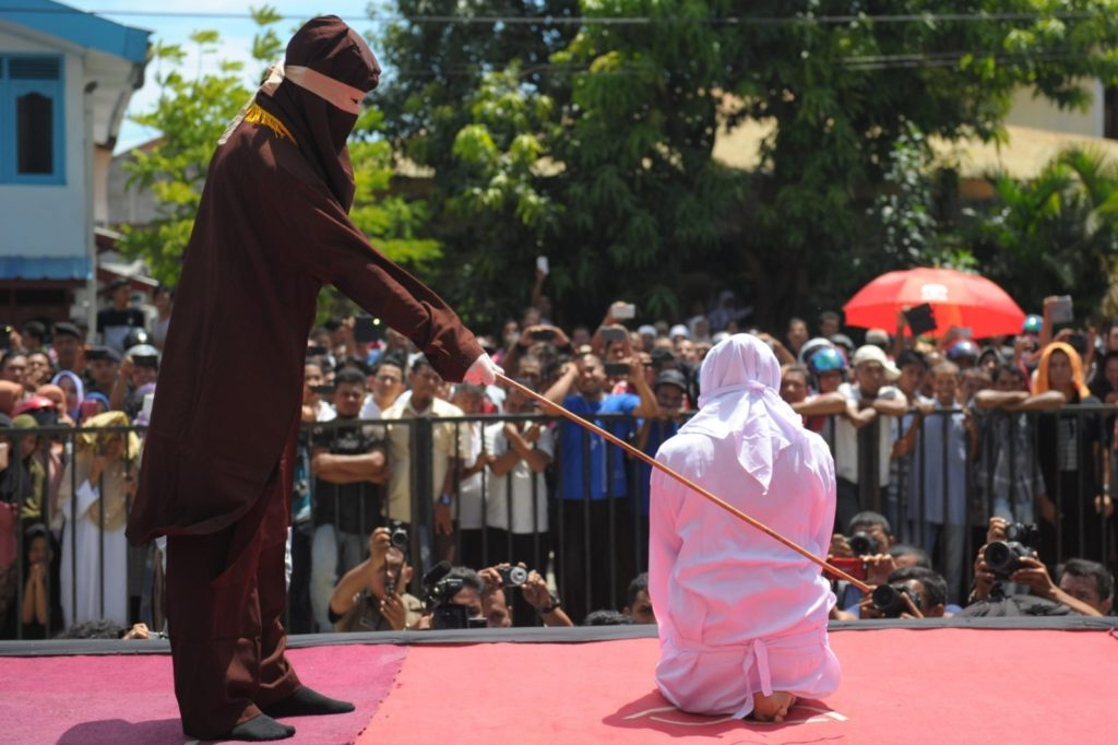 A religious officer canes an Acehnese youth onstage as punishment for dating outside of marriage, which is against sharia law, outside a mosque in Banda Aceh on August 1, 2016. The strictly Muslim province, Aceh has become increasingly conservative in recent years and is the only one in Indonesia implementing Sharia law. / AFP / CHAIDEER MAHYUDDIN (Photo credit should read CHAIDEER MAHYUDDIN/AFP/Getty Images)