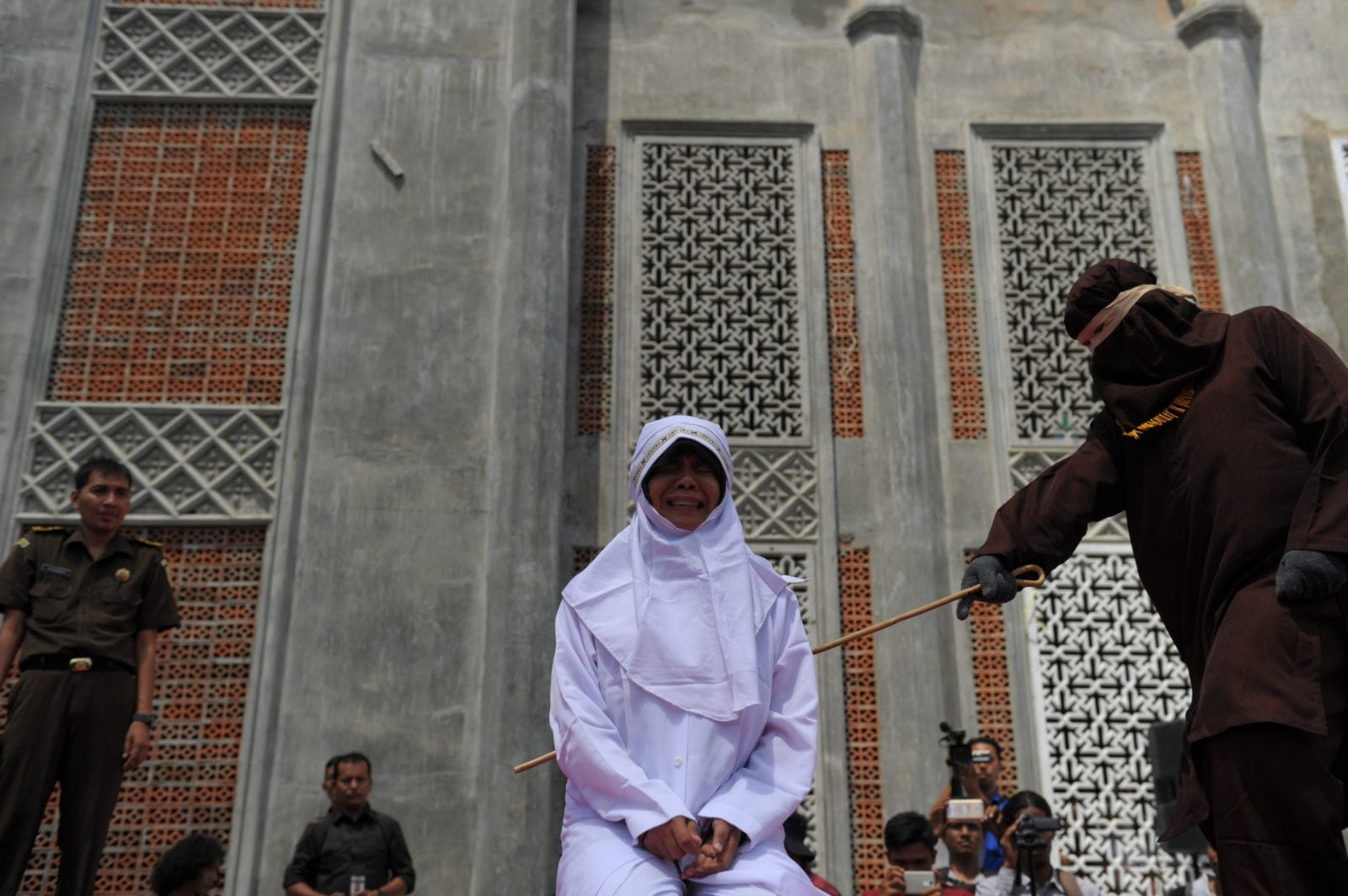 TOPSHOT - A religious officer canes an Acehnese youth onstage as punishment for dating outside of marriage, which is against sharia law, outside a mosque in Banda Aceh on August 1, 2016. The strictly Muslim province, Aceh has become increasingly conservative in recent years and is the only one in Indonesia implementing Sharia law. / AFP / CHAIDEER MAHYUDDIN (Photo credit should read CHAIDEER MAHYUDDIN/AFP/Getty Images)