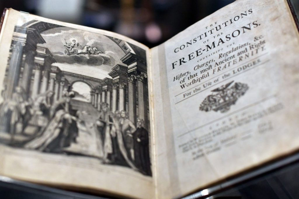 LONDON, ENGLAND - SEPTEMBER 28: A book by James Anderson titled 'The Constitutions of the Free-Masons' dated 1723, is displayed by a member of staff during a press preview for the opening of a gallery titled 'Three Centuries of English Freemasonry' at the Library and Museum of Freemasonry on September 28, 2016 in London, England. To mark Freemasonry's 300th anniversary, a new permanent gallery space is being opened and features items including Winston Churchill's Masonic apron and the Grand Master's Throne. (Photo by Carl Court/Getty Images)