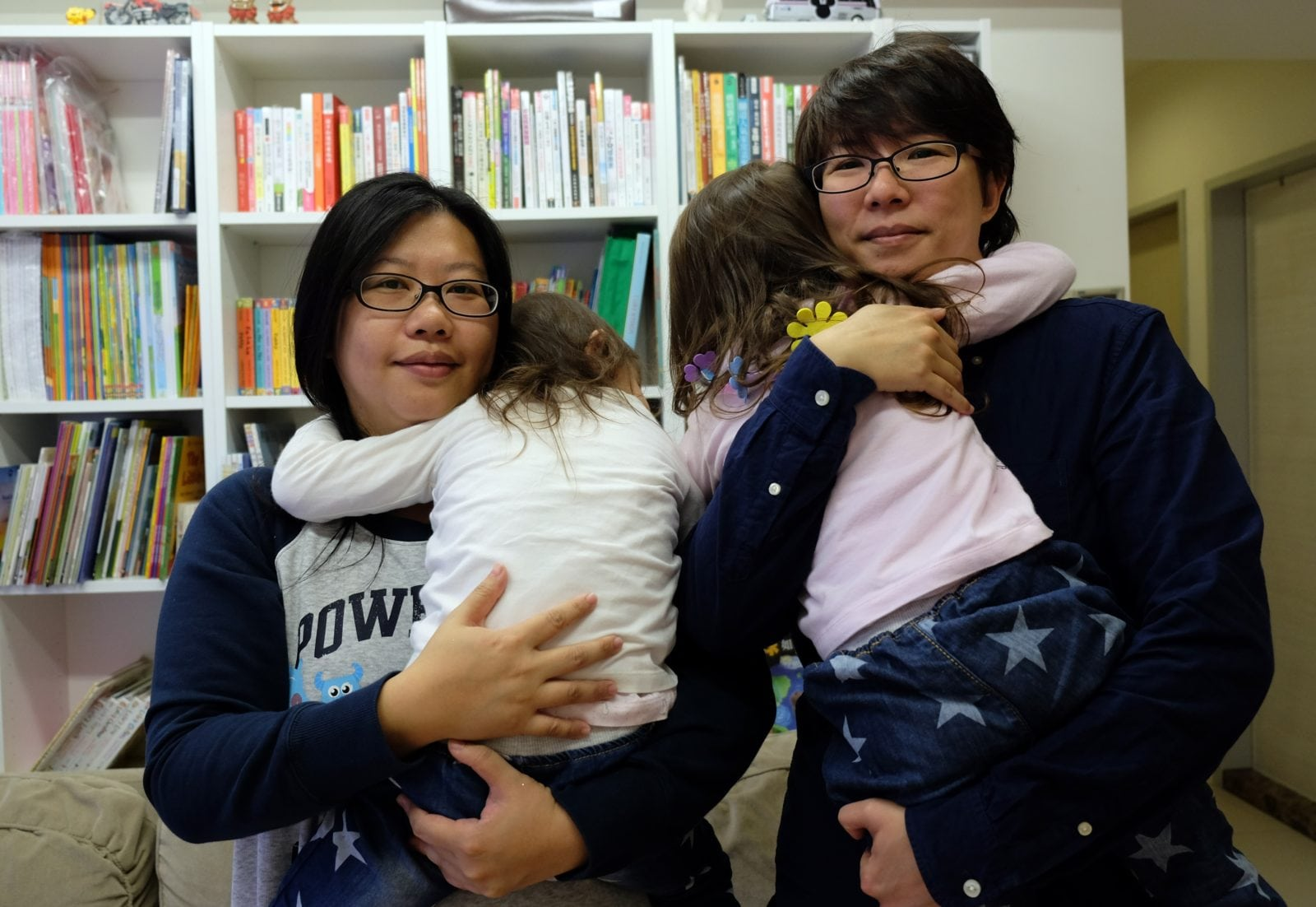 Same-sex couple Hope Chen (L), 37, and Zoro Wen, 34, pose with their twin daughters at their home in Taoyuan, northern Taiwan