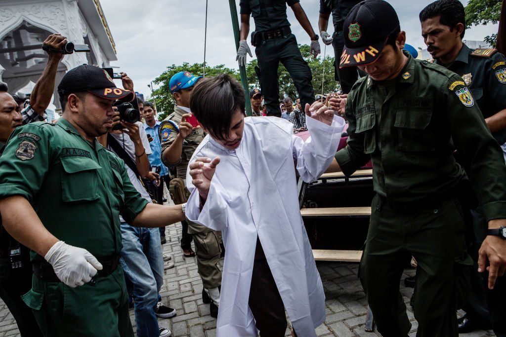 Indonesian man escorted after public caning for having gay sex BANDA ACEH, INDONESIA - MAY 23: An indonesian man escorted by the sharia police after get caning in public from an executor known as 'algojo' for having gay sex, which is against Sharia law at Syuhada mosque on May 23, 2017 in Banda Aceh, Indonesia. The two young gay men, aged 20 and 23, were caned 85 times each in the Indonesian province of Aceh during a public ceremony after being caught having sex last week. It was the first time gay men have been caned under Sharia law as gay sex is not illegal in most of Indonesia except for Aceh, which is the only province which exercises Islamic law. The punishment came a day after the police arrested 141 men at a sauna in the capital Jakarta on Monday due to suspicion of having a gay sex party, the latest crackdown on homosexuality in the country. (Photo by Ulet Ifansasti/Getty Images)