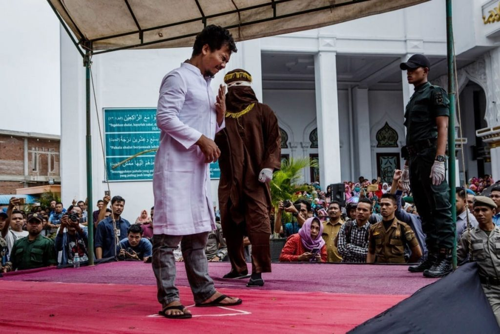 BANDA ACEH, INDONESIA - MAY 23: An acehnese man gets caning in public from an executor known as 'algojo' for spending time with a woman who is not his wife, which is against Sharia law at Syuhada mosque on May 23, 2017 in Banda Aceh, Indonesia. Indonesia's Aceh Province, on the northern tip of Sumatra island, is among the only place in the Muslim-majority country which implements the strict version of Sharia Law. Public canings take place regularly in Aceh for a range of offenses from adultery to homosexuality to selling alcohol, while women are required to dress modestly and Shariah police officers patrol the streets and conduct raids to hunt for immoral activities. More than 90 per cent of the 255 million people who live in Indonesia describe themselves as Muslim, but the vast majority practice a moderate form. According to reports, the Shariah Law in Aceh began in 2001, after receiving authorization from Indonesia's central government, which was intent on calming separatist sentiment in the conservative region while today. (Photo by Ulet Ifansasti/Getty Images)