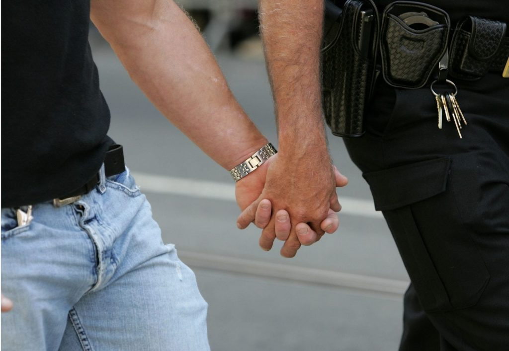 A same-sex couple holding hands, representing the gay couples who met online
