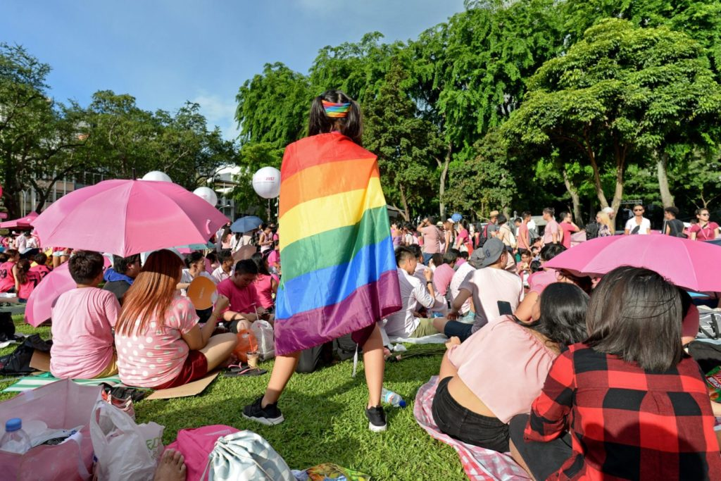 "A supporter wrapped in a rainbow flag attends the annual ""Pink Dot"" event in a public show of support for the LGBT community at Hong Lim Park in Singapore on July 1, 2017. Thousands of Singaporeans took part in the gay-rights rally on July 1. / AFP PHOTO / Roslan RAHMAN (Photo credit should read ROSLAN RAHMAN/AFP/Getty Images)"