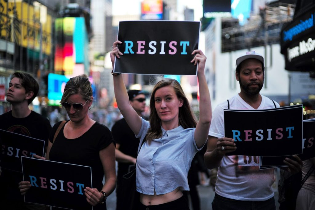 """Protesters display placards against US President Donald Trump during a demonstration in front of the US Army career center in Times Square, New York, on July 26, 2017. Trump announced on July 26 that transgender people may not serve """"in any capacity"""" in the US military, citing the """"tremendous medical costs and disruption"""" their presence would cause. / AFP PHOTO / Jewel SAMAD (Photo credit should read JEWEL SAMAD/AFP/Getty Images)"""
