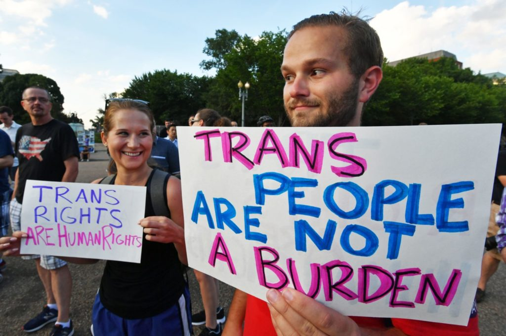 """Protesters gather in front of the White House on July 26, 2017, in Washington, DC. Trump announced on July 26 that transgender people may not serve """"in any capacity"""" in the US military, citing the """"tremendous medical costs and disruption"""" their presence would cause. / AFP PHOTO / PAUL J. RICHARDS (Photo credit should read PAUL J. RICHARDS/AFP/Getty Images)"""