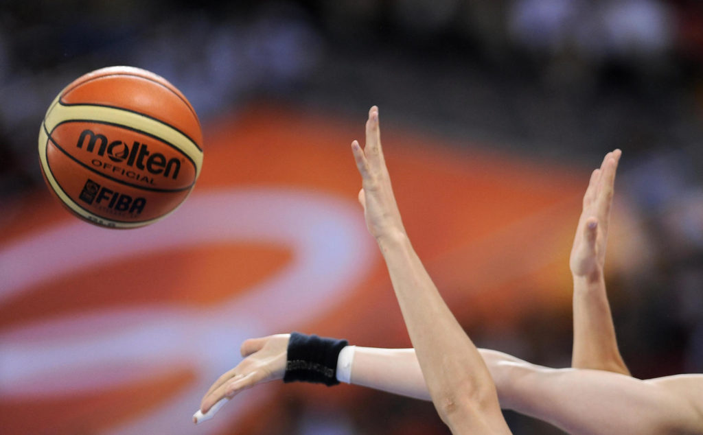 Women's hands grasping at a basketball